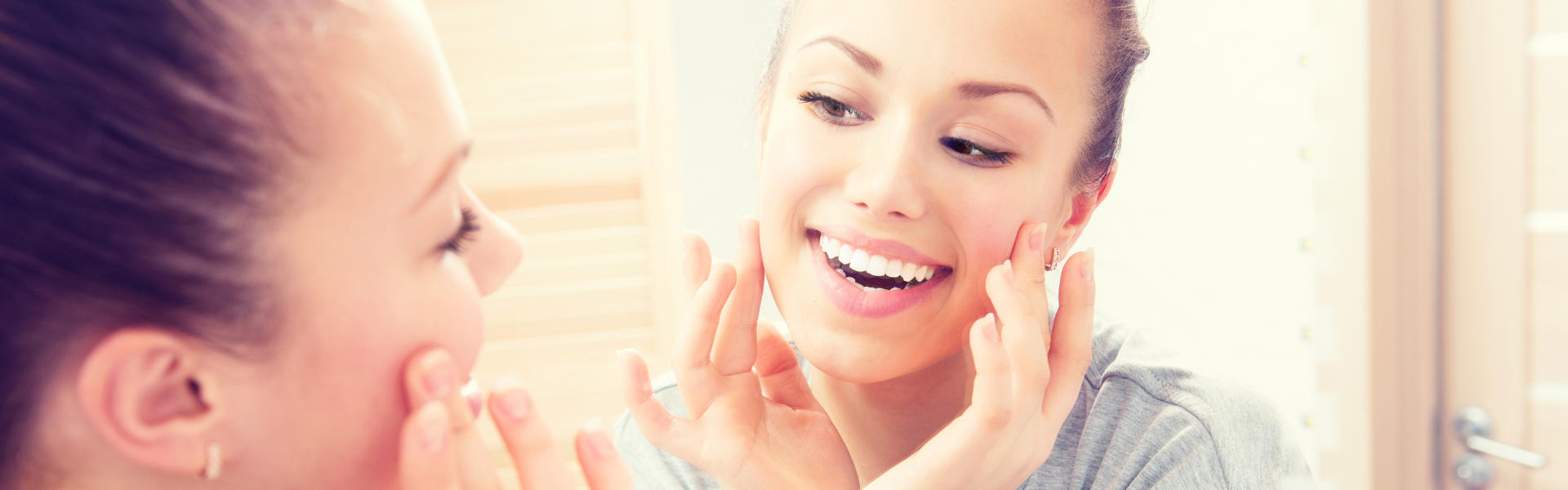 Cheerful young woman in front of a mirror looking at her perfect teeth after having Cerec Crowns applied