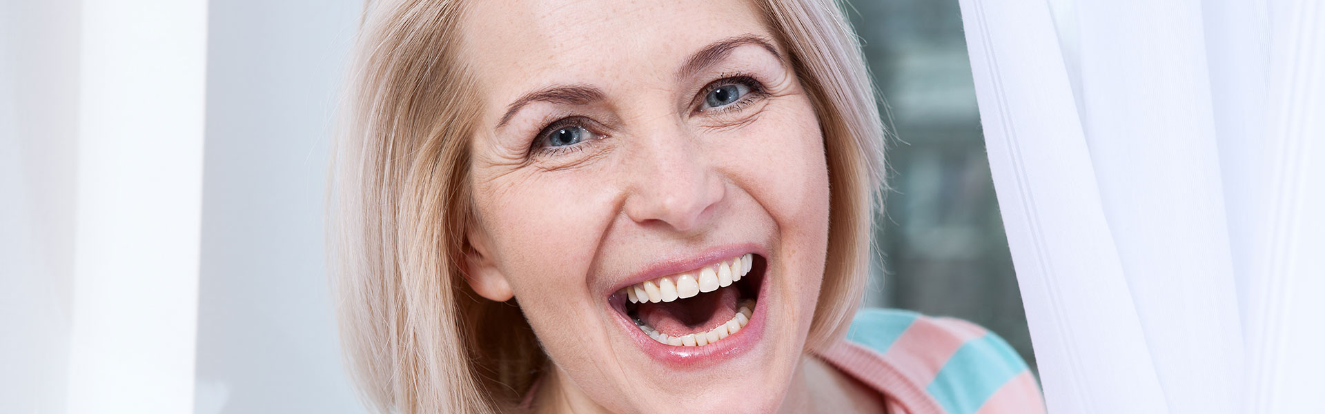smiling broadly mature woman with perfect teeth