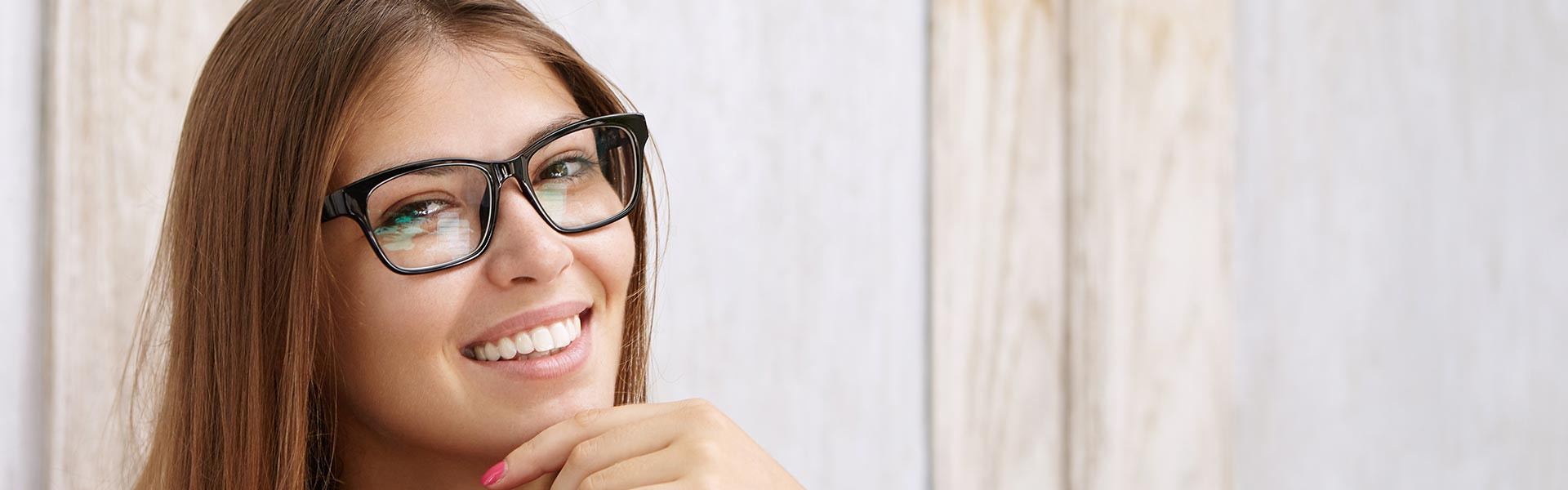 young woman wearing glasses showing perfect teeth with porcelain veneers applied in her smile